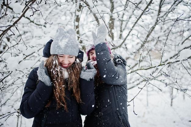 Deux amis filles drôles s'amusant au jour d'hiver enneigé près des arbres couverts de neige. Photo Premium