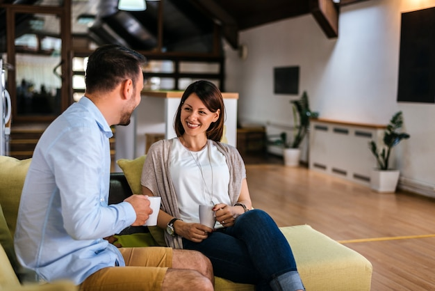 Deux amis heureux buvant du café et discutant sur le canapé à la maison dans le salon Photo Premium