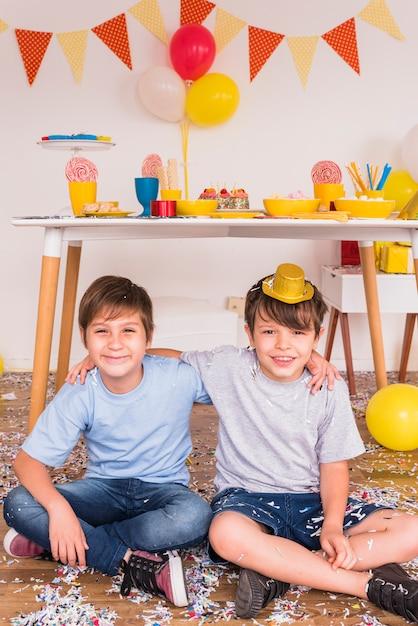Deux amis hommes souriants, assis avec des confettis sur le plancher de bois franc Photo gratuit