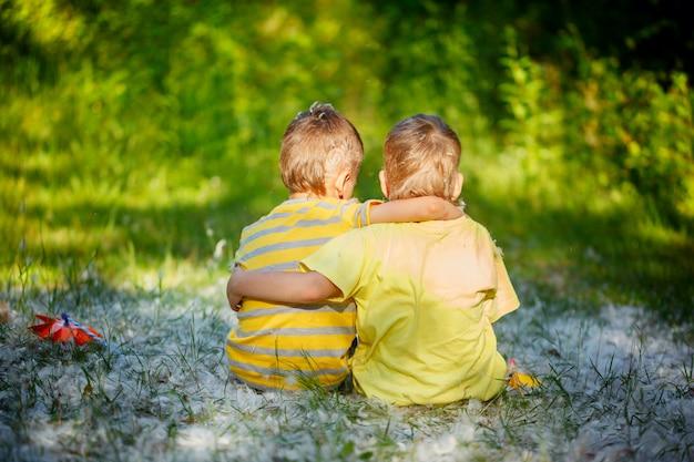 Deux amis de petit garçon s'embrassent dans un jardin d'été. brothe Photo Premium