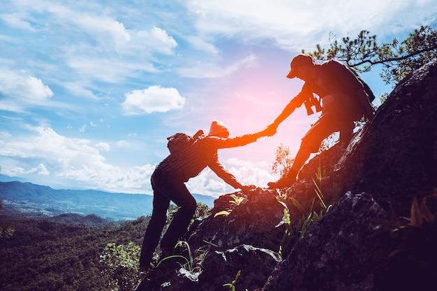 Deux amis s'entraident et travaillent en équipe pour atteindre le sommet des montagnes. Photo Premium