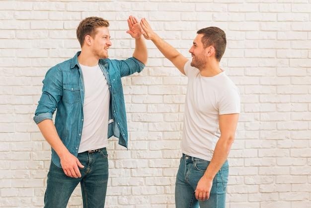Deux Amis De Sexe Masculin Se Donnant Haut Cinq Contre Un Mur De Briques Blanches Photo gratuit
