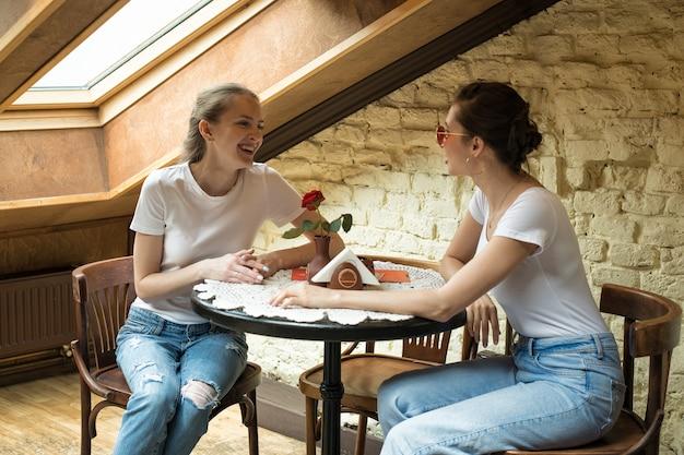 Deux Amis Sont Assis à Table Et Rient. Rencontre Amicale, Potins. Concept D'amitié Photo Premium