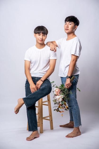 Deux Amoureux, Les Mains Posées Sur Leurs épaules Et Assis Sur Une Chaise. Photo gratuit