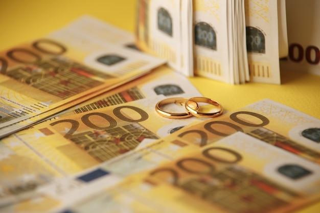 Deux Anneaux De Mariage Et De L'argent Comme Symbole D'une Alliance Coûteuse Photo Premium