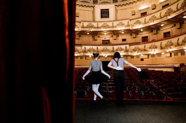 Deux artistes de mime s'inclinant dans un auditorium vide Photo gratuit