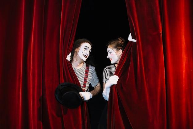 Deux artistes mimes derrière un rideau rouge se regardant Photo gratuit