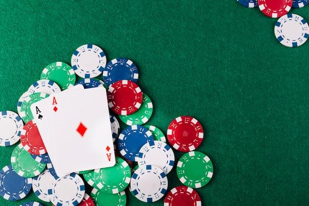 Deux as jouant aux cartes et jetons sur une table de poker verte Photo gratuit