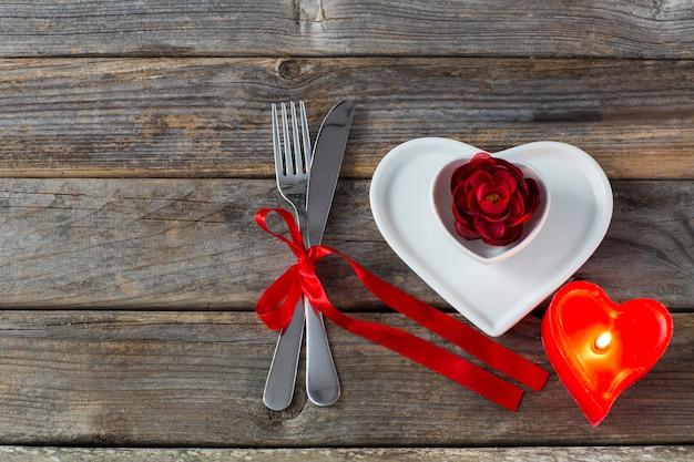 Deux assiettes en forme de coeur, un bouton de rose rouge, une bougie en forme de coeur rouge et des couverts noués avec un ruban rouge Photo Premium