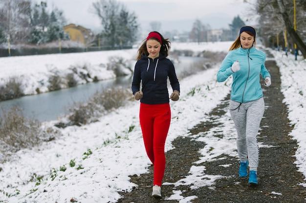 Deux athlètes féminines jogging dans la rue près de la rivière en hiver Photo gratuit