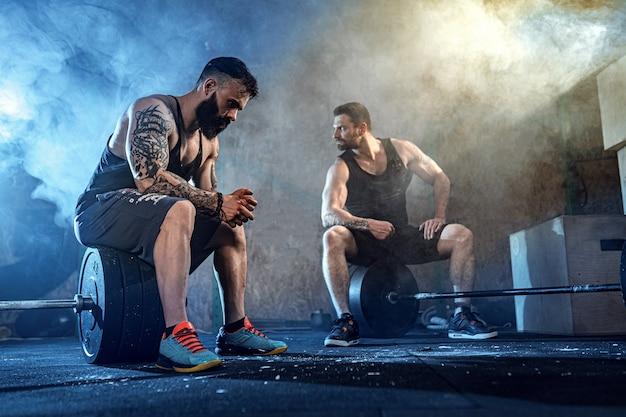 Deux Athlètes Musclés Tatoués Barbu S'entraînant Au Gymnase Photo Premium