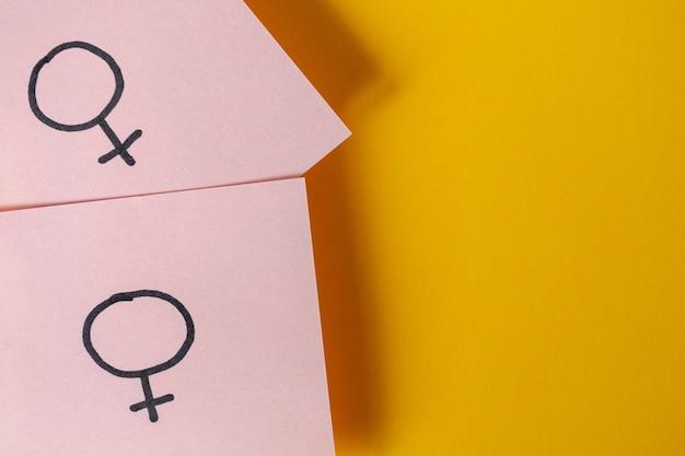 Deux autocollants roses avec les symboles de sexe vénus au-dessus d'un fond jaune Photo Premium