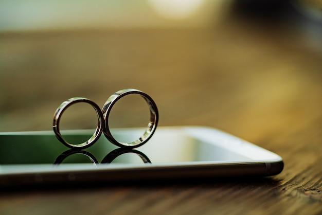Deux bagues en or sont au téléphone dans la pièce. anneaux en forme de huit infinis Photo Premium
