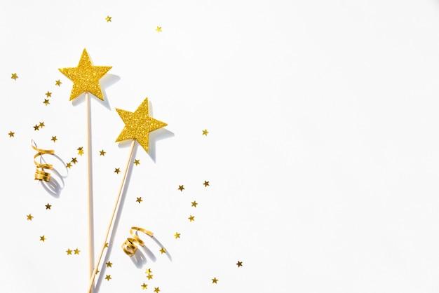 Deux baguettes magiques de parti d'or, des paillettes et des rubans sur un blanc Photo Premium