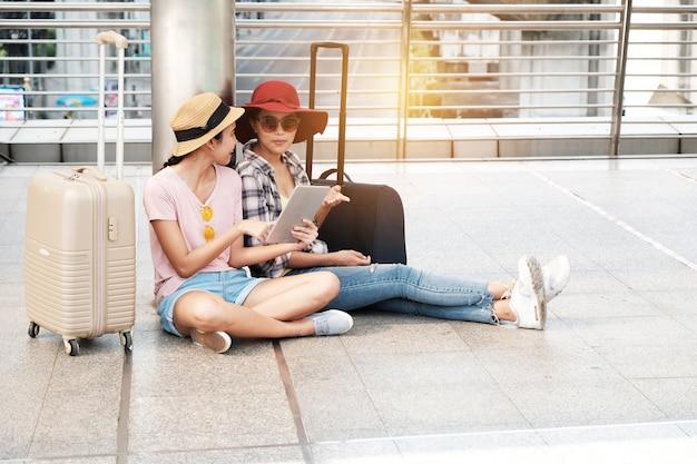 Deux Beaux Touristes Se Tiennent La Carte Parlante. Photo Premium