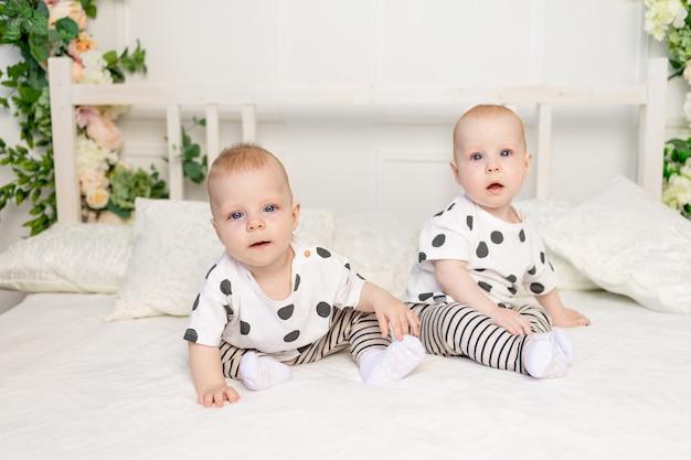 Deux Bébés Jumeaux Assis Sur Le Lit Dans Les Mêmes Vêtements, Relation Frère-sœur, Vêtements à La Mode Pour Enfants De Jumeaux, Concept De Mariage Et D'amitié Photo Premium