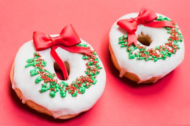 Deux beignets décorés disposés sur fond rouge Photo gratuit