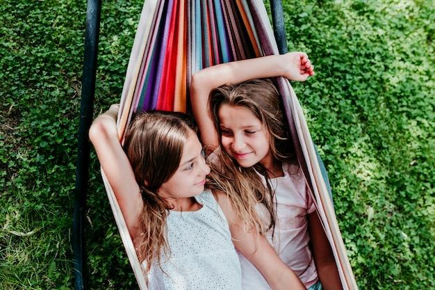 Deux Belles Adolescentes Allongées Sur Un Hamac Coloré Dans Le Jardin. Photo Premium