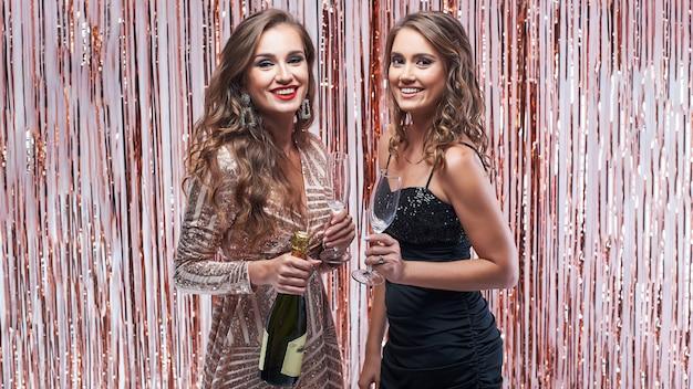 Deux Belles Femmes élégantes Buvant Du Champagne Contre Une Décoration étincelante Photo Premium