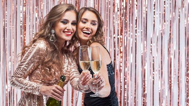 Deux Belles Femmes élégantes Tinter Les Verres De Champagne. Photo Premium