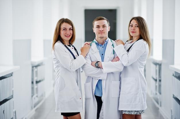Deux Belles Femmes Médecins Et Un Homme En Blouse Blanche Posant à L'hôpital Avec Stéthoscope. Photo Premium