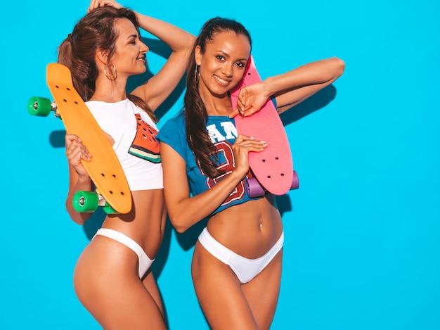 Deux Belles Femmes Sexy Souriantes En Sous-vêtements D'été Et Sujet. Filles à La Mode. Des Modèles Positifs S'amusent Avec Des Planches à Roulettes Colorées. Isolé Photo gratuit