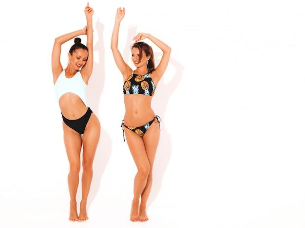 Deux Belles Femmes Souriantes Sexy En Lingerie De Natation. Modèles Chauds à La Mode S'amusant. Filles Isolées, Levant Les Mains, Pleine Longueur Photo gratuit