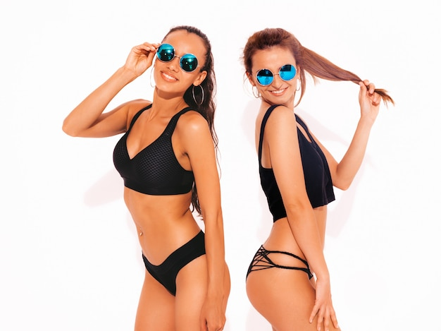 Deux Belles Femmes Souriantes Sexy En Lingerie Noire. Modèles Chauds à La Mode S'amusant. Filles Isolées En Lunettes De Soleil Photo gratuit