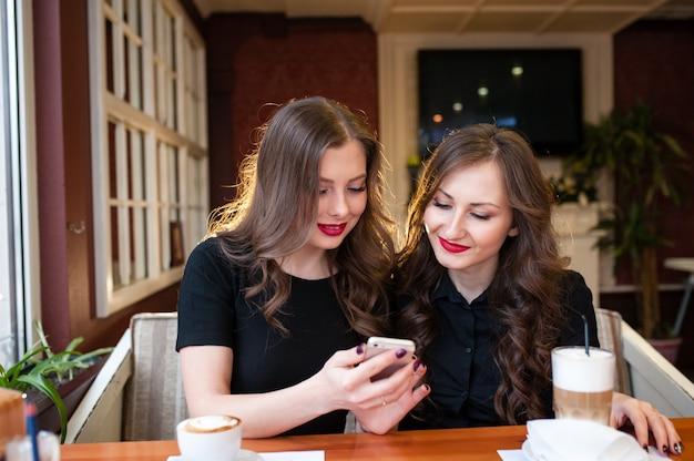 Deux belles filles boivent du café et regardent dans le téléphone Photo Premium