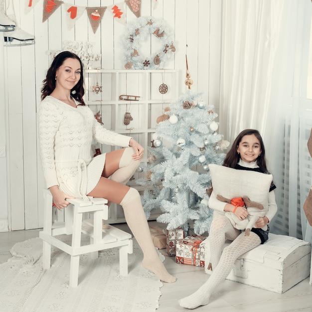 Deux Belles Filles, Mère Et Fille Implantées Dans Une Pièce Décorée De Noël. Photo Premium