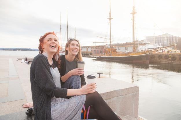 Deux belles filles nordiques profitant de la vie dans le port d'oslo Photo Premium