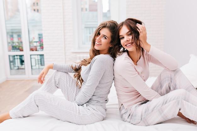 Deux Belles Filles En Pyjama Assis Dos à Dos Sur Un Lit Blanc Dans Une Pièce Lumineuse. Ils Sourient. Photo gratuit