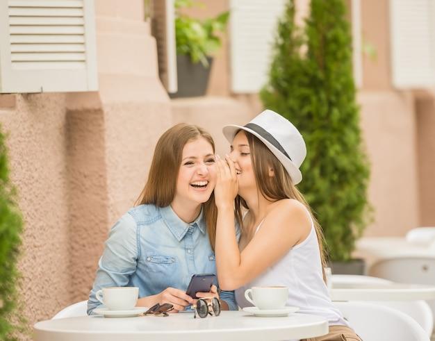 Deux belles jeunes femmes assises au café d'été. Photo Premium