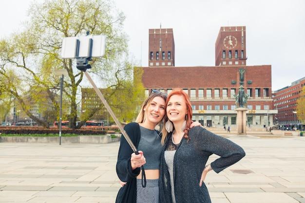 Deux belles jeunes femmes prenant un selfie à oslo Photo Premium