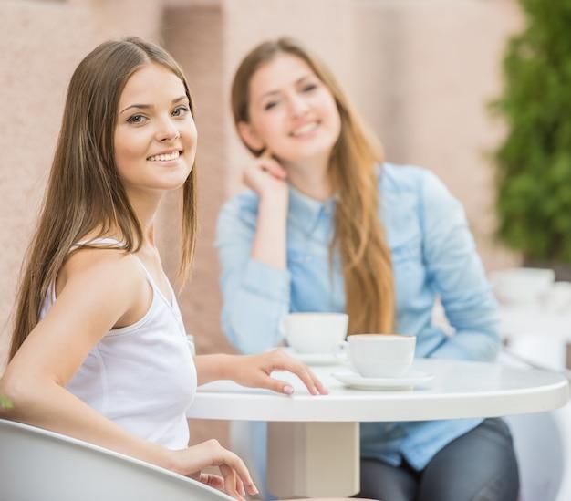 Deux belles jeunes femmes se réunissant pour un café. Photo Premium