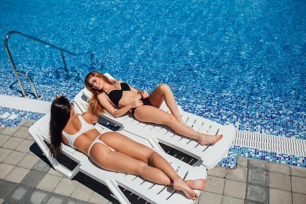 Deux Belles Jeunes Filles Avec De Belles Figures Prennent Le Soleil Au Bord De La Piscine Et Parlent Photo Premium