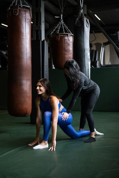 Deux Belles Jeunes Filles Faisant Du Fitness Dans Une Salle De Sport. étirement Des Muscles Du Dos Et Des Jambes. Photo gratuit