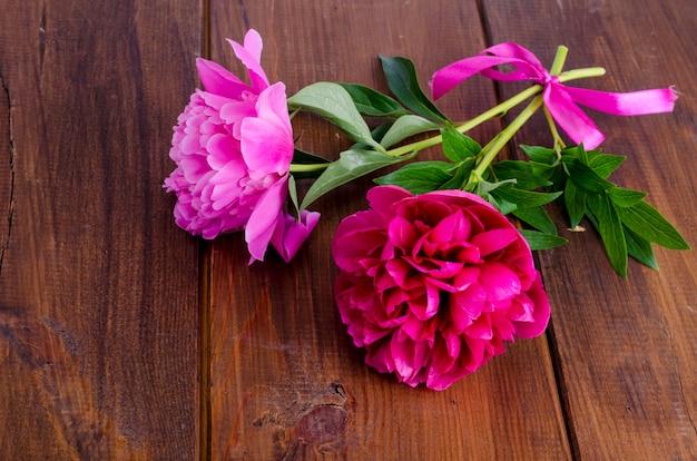 Deux belles pivoines avec ruban sur table en bois Photo Premium