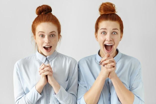 Deux Belles Travailleuses Surprises Aux Cheveux Roux, Vêtues Des Mêmes Chemises Photo gratuit