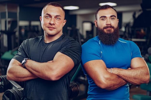 Deux Bodybuilders Hommes Ajustement Souriant Debout Côte à Côte Dans Une Salle De Sport Photo Premium