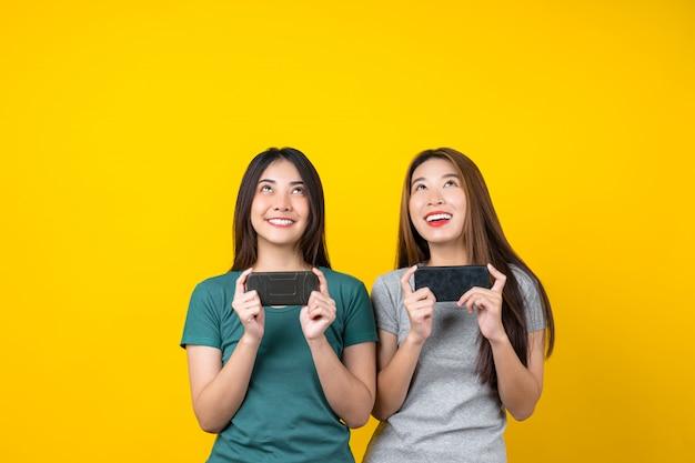 Deux Bonheur Asiatique Souriant Jeune Femme Gamer à L'aide De Téléphone Mobile Intelligent Et Jouer à Des Jeux Sur Le Mur De Couleur Jaune Isolé Photo Premium