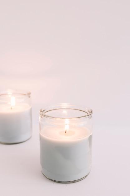 Deux bougies allumées dans des bougeoirs en verre Photo gratuit