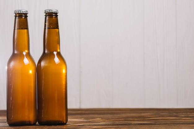 Deux bouteilles de bière sur une surface en bois Photo gratuit