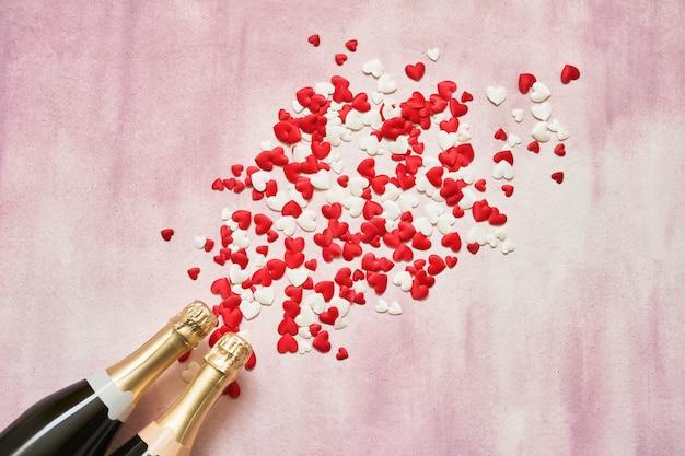 Deux bouteilles de champagne avec des coeurs rouges et blancs sur fond rose. Photo Premium
