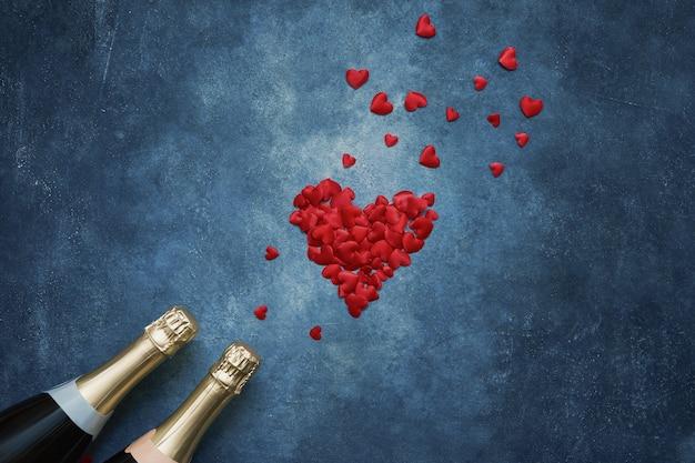 Deux bouteilles de champagne avec des coeurs rouges sur fond bleu. Photo Premium