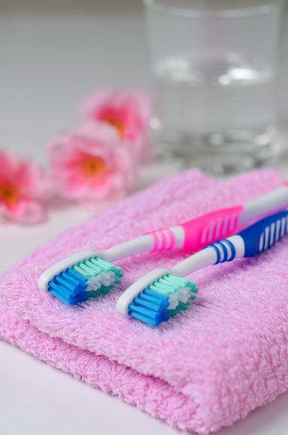 Deux brosses à dents roses sur une serviette rose. l'eau dans un bécher en verre Photo Premium