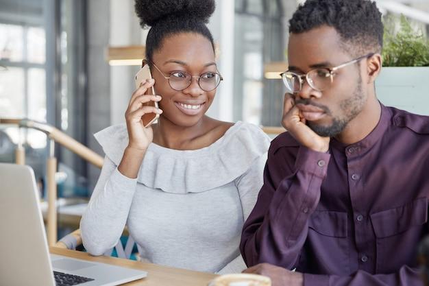 Deux Camarades De Groupe Afro-américains Se Réunissent Pour Faire Fonctionner Le Projet Ou Se Préparer Pour Les Cours: Une Femme Heureuse à La Peau Sombre Parle Avec Un Ami Via Un Téléphone Portable Photo gratuit