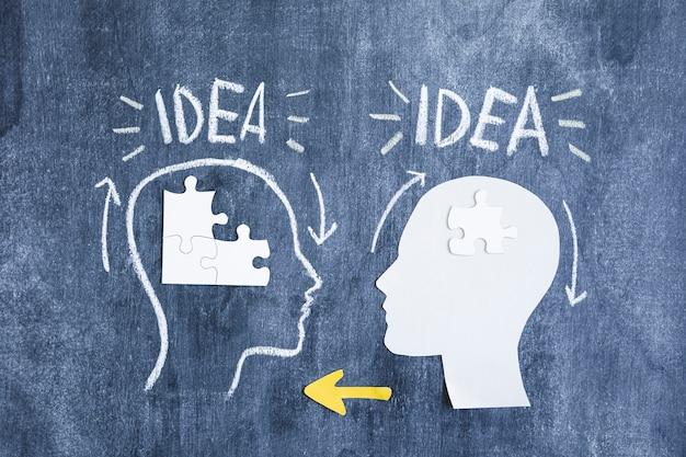 Deux cerveaux échangeant les informations avec des morceaux de puzzle et des flèches jaunes sur le tableau noir Photo gratuit