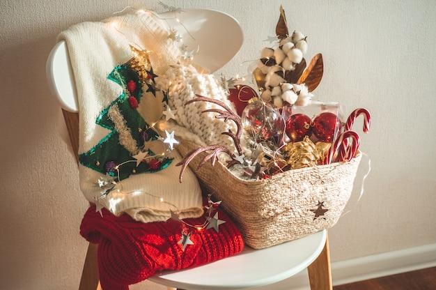 Deux Chandails D'hiver Posés Sur Une Chaise Avec Un Panier De Décorations De Noël. Photo Premium