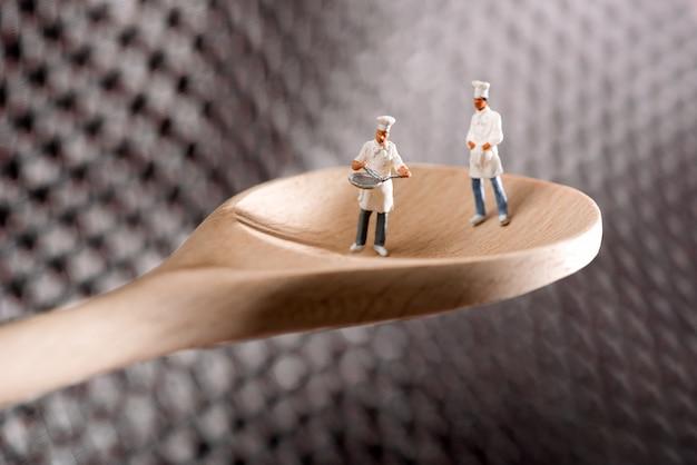 Deux chefs miniatures ou cuisine sur une cuillère en bois Photo Premium